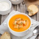 Pumpkin soup with pumpkin seeds and croutons on the rustic wooden table